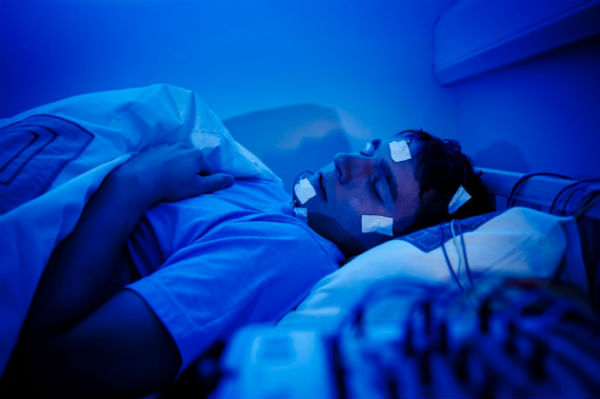 A man hooked up to equipment to study his sleep patterns
