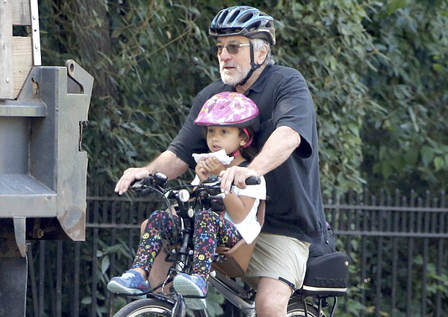 Robert De Niro and daughter riding a bike