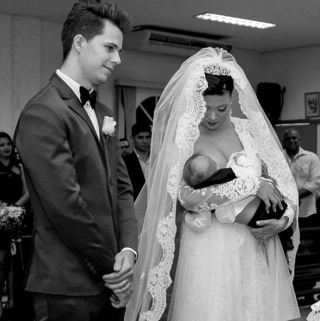 A mother breastfeeding her baby at her wedding