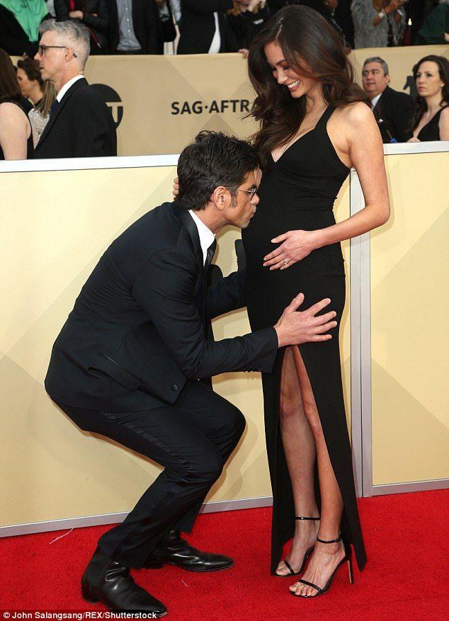 John Stamos kissing Caitlin McHugh's baby bump