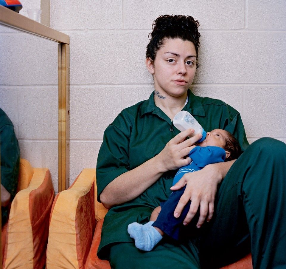 A woman in prison feeding her baby
