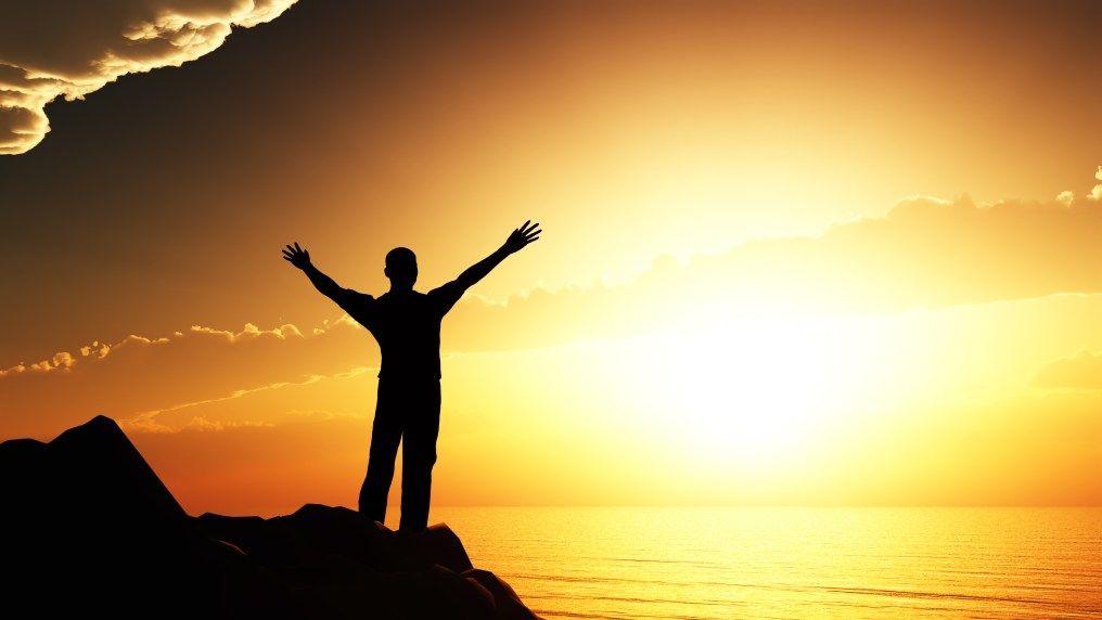 Someone raising their arms on a mountain