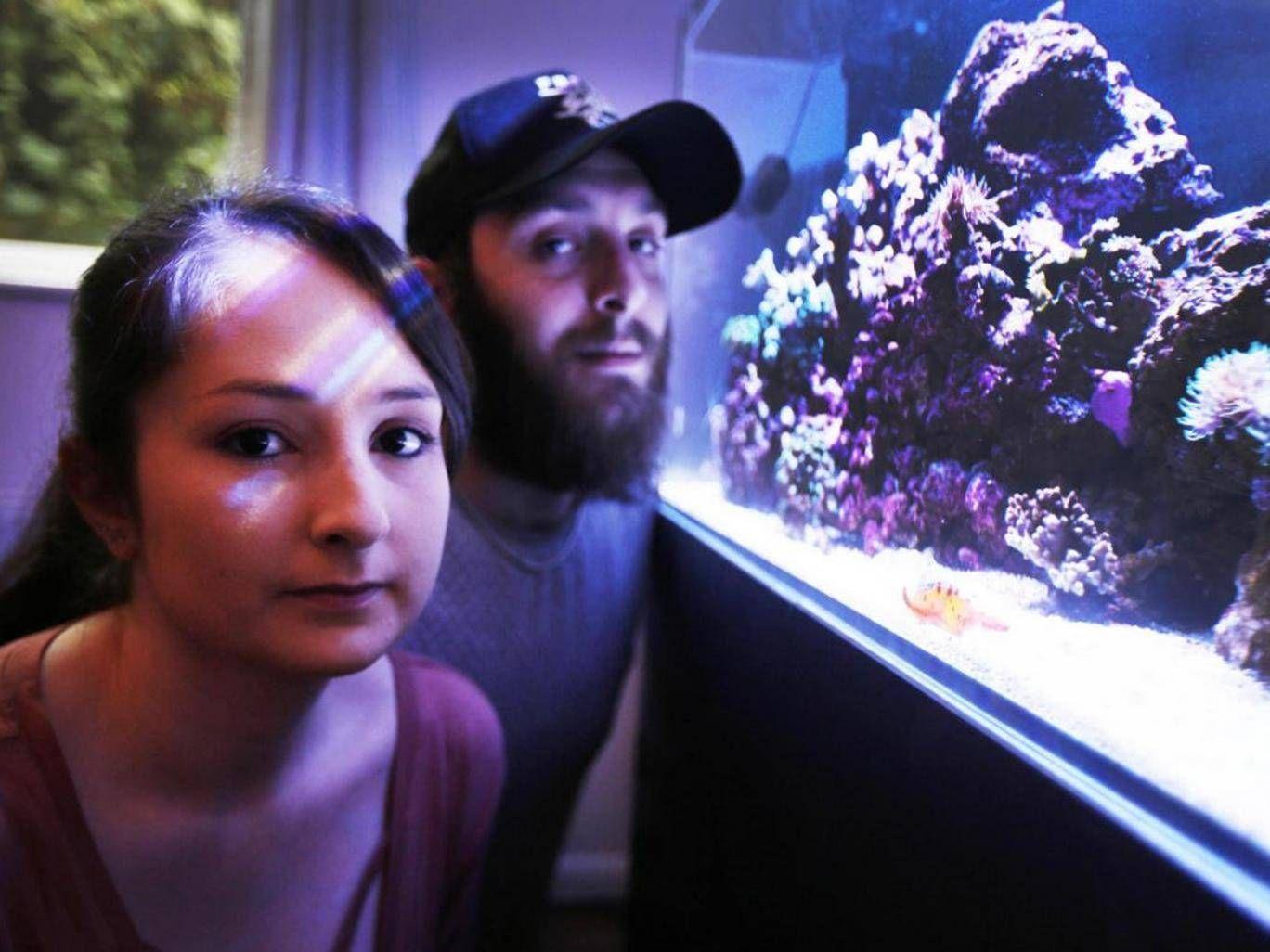 Chris Matthews and his girlfriend beside a fish tank