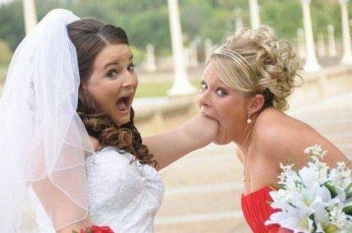 A bridesmaid with the bride's arm in her mouth