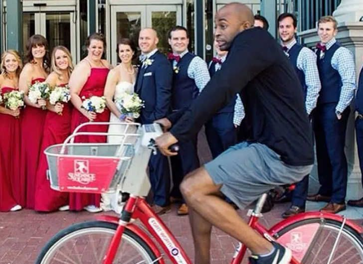 A man riding a bike in front of a wedding photo
