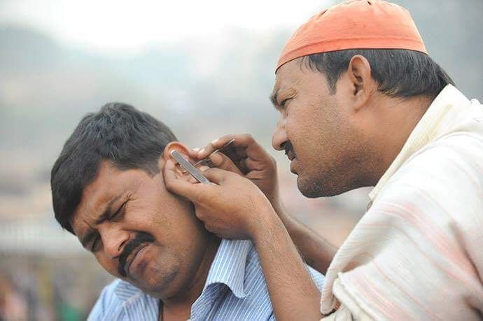 A man cleaning out another man's ear