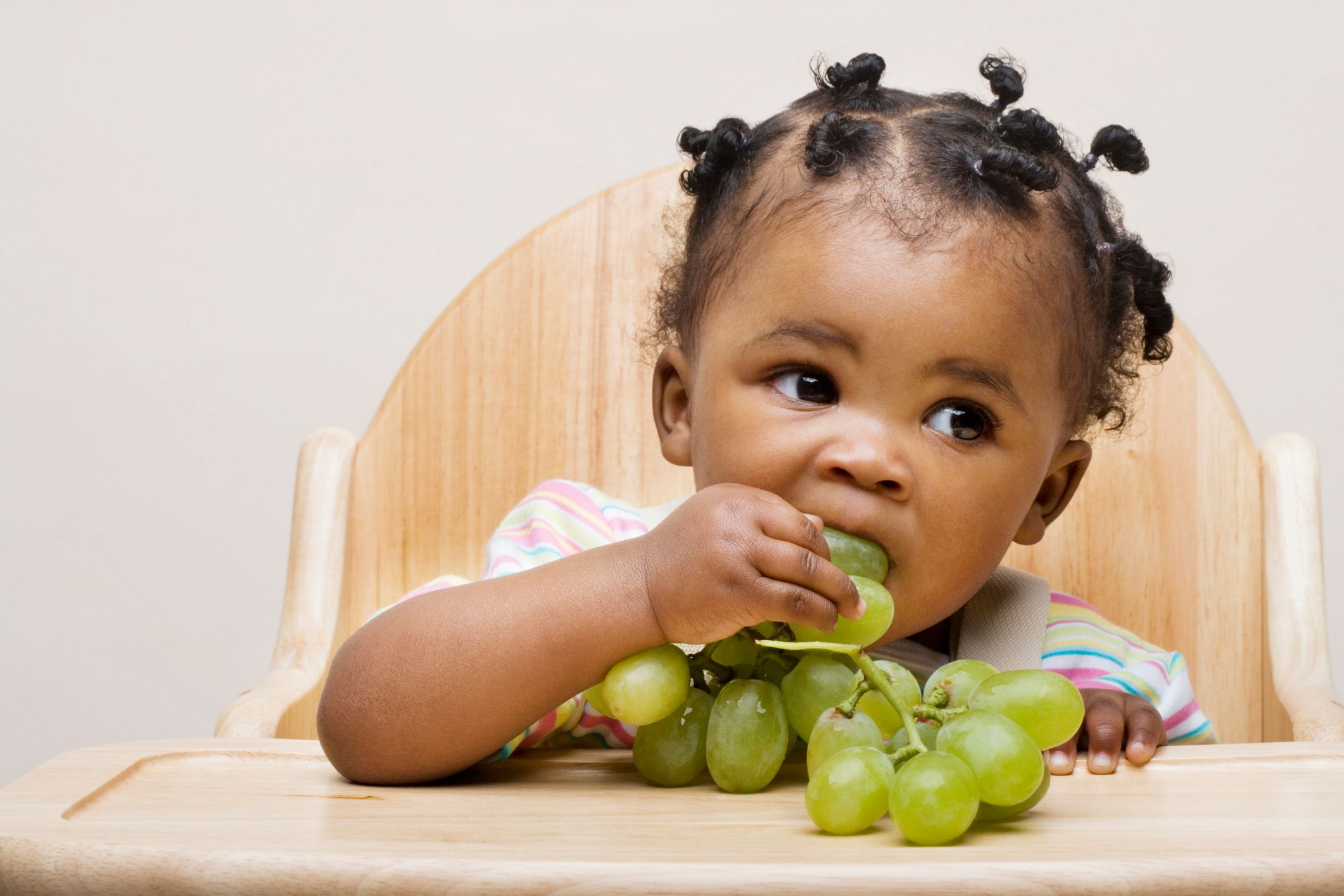 A baby eating grapes