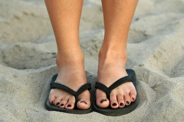Someone standing in sand in flip-flops