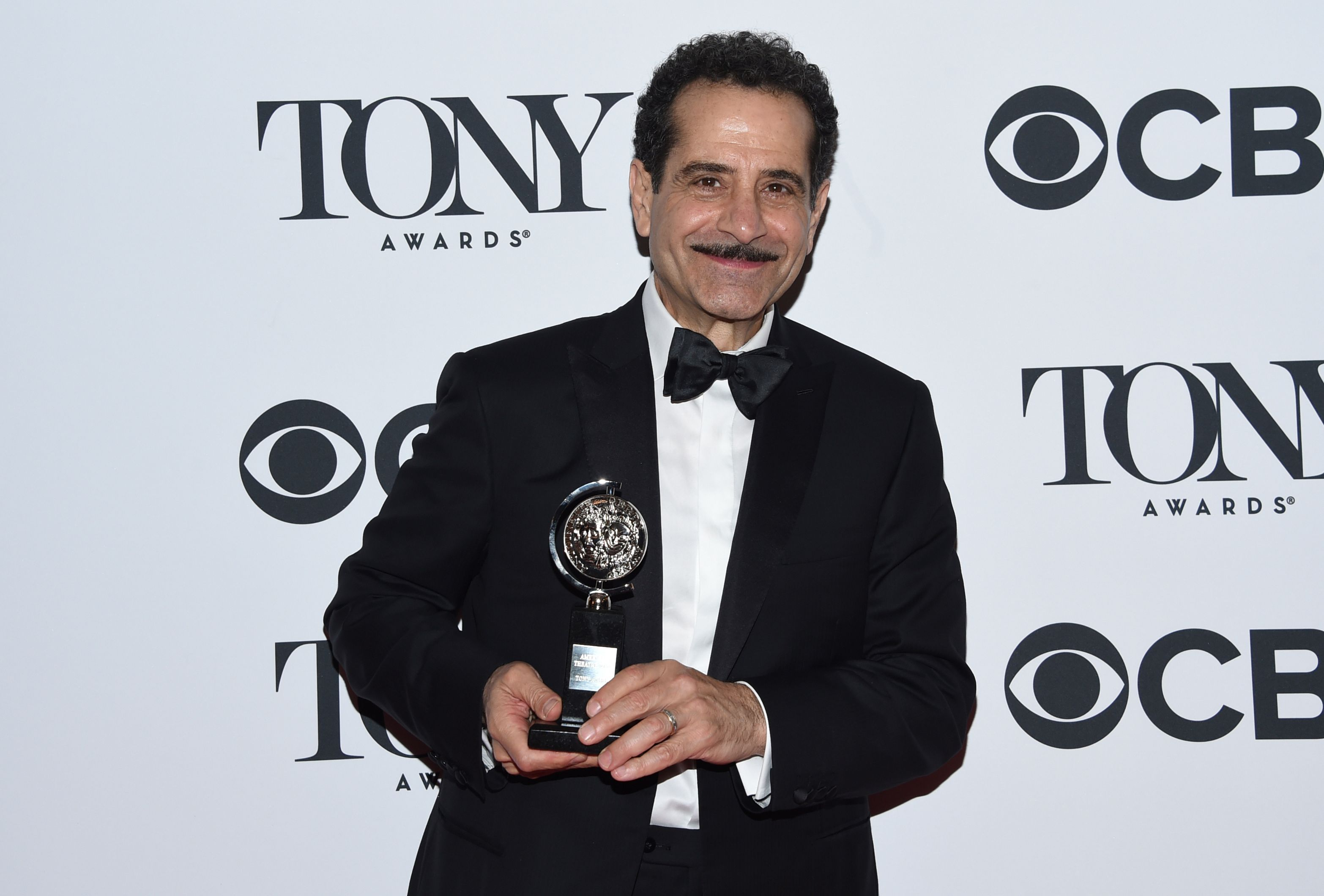 """Tony Shalhoub poses in the press room with the award for leading actor in a musical for """"The Band's Visit"""" at the 72nd annual Tony Awards"""