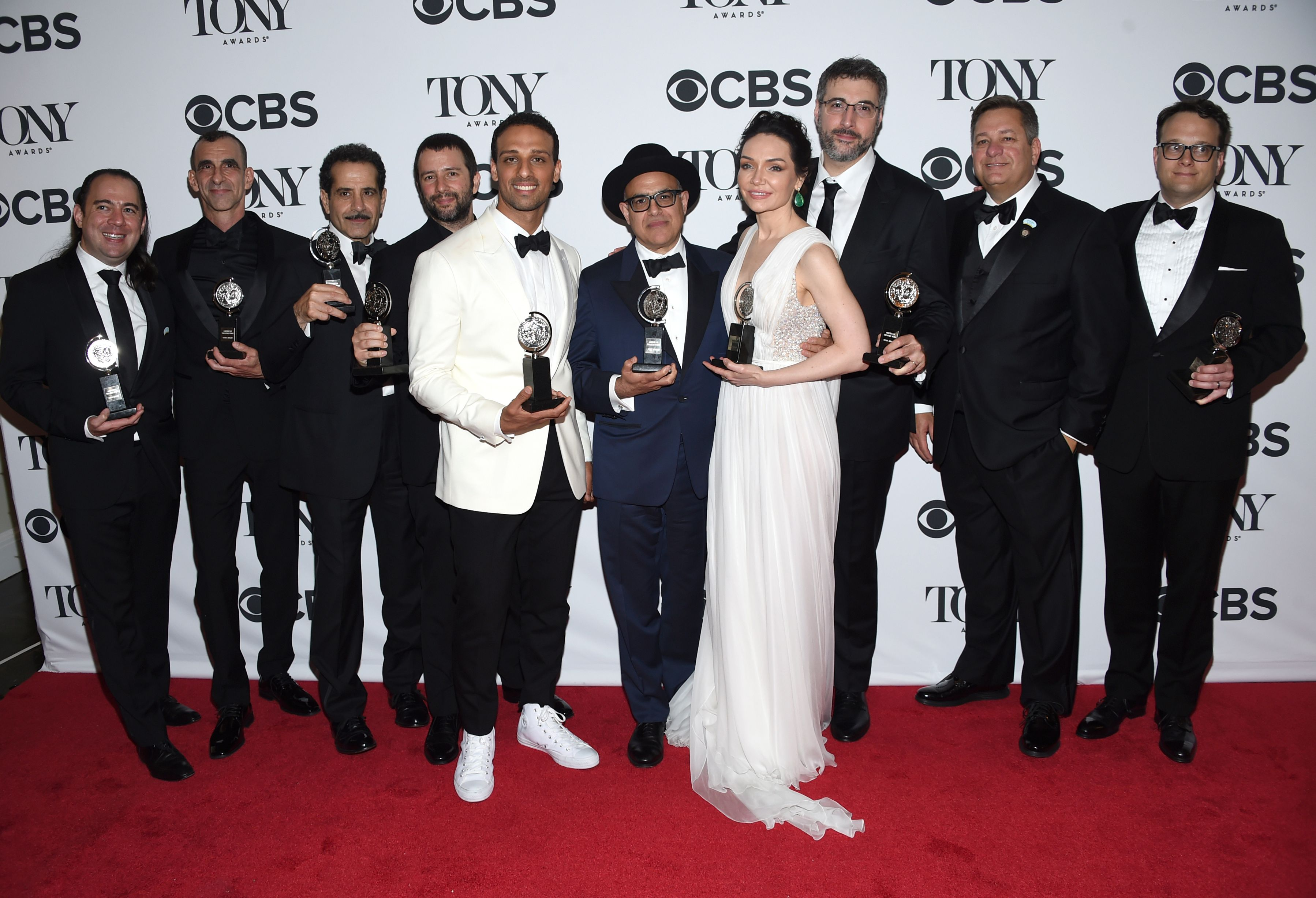 """Cast and crew of """"The Band's Visit"""" pose in the press room with the award for best musical at the 72nd annual Tony Awards"""