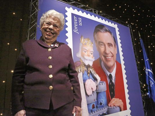 Joanne Rogers beside a stamp of her husband's face