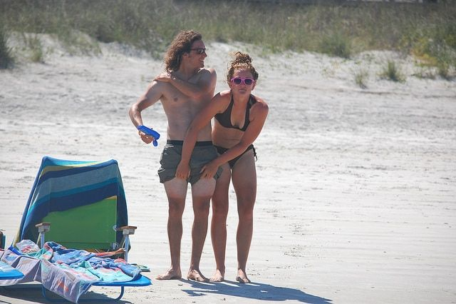A woman covering a man's sun tan lines