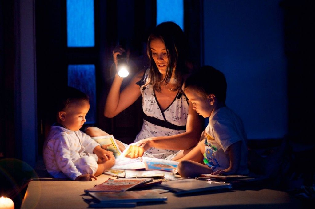 A mother using a flashlight with her sons