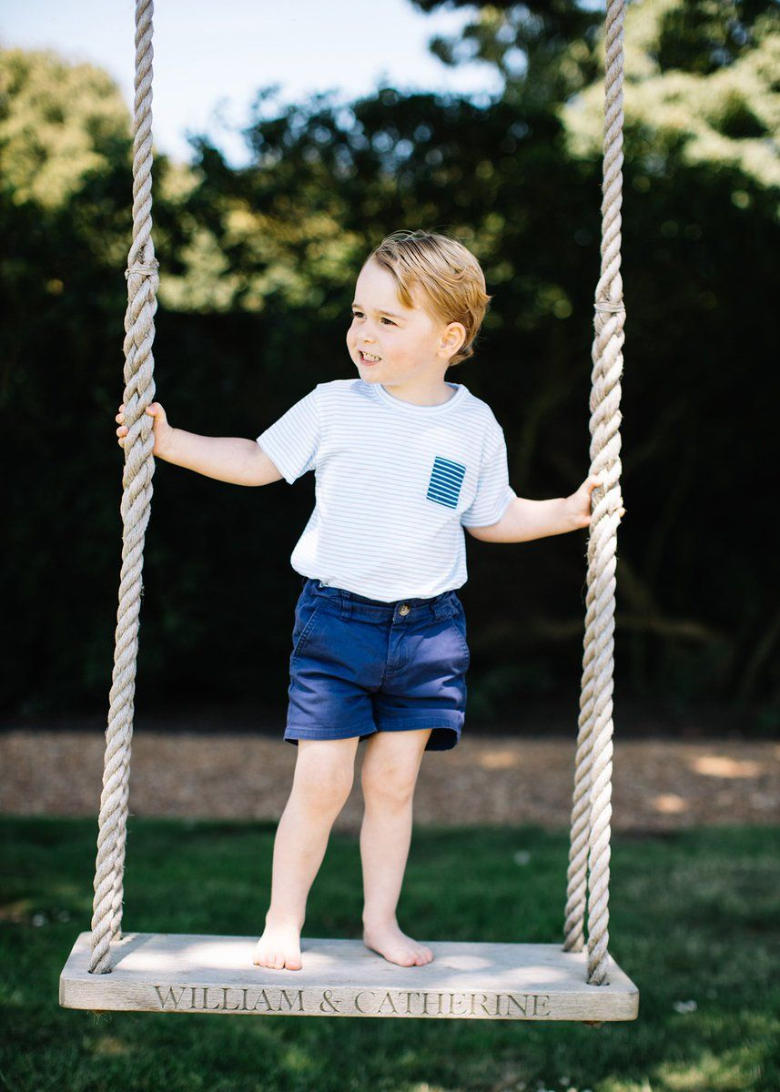 Prince George standing on a swing
