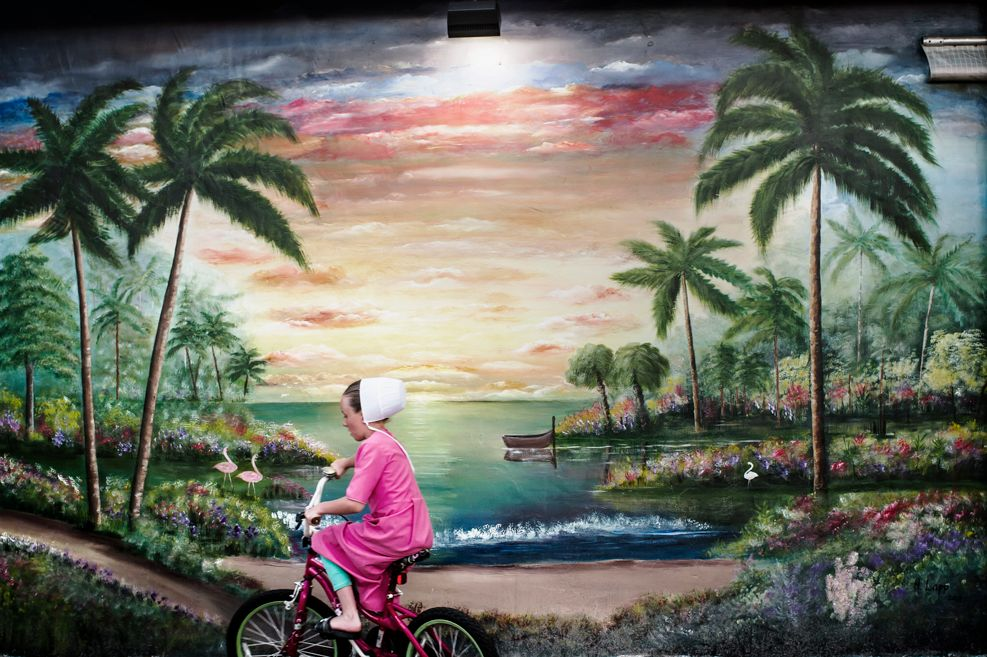 A girl riding her bike in from of a mural