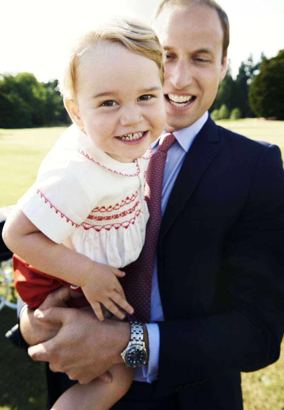 Prince William holding a smiling Prince George