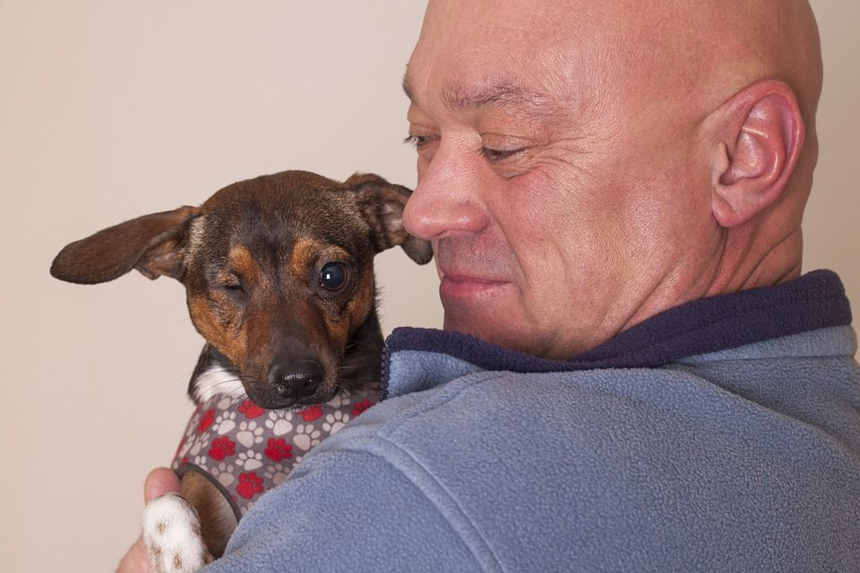An owner cuddling his dog