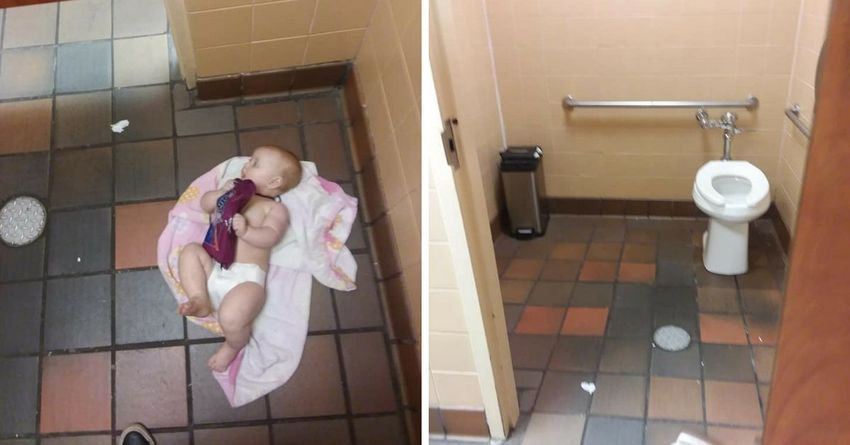 Baby being changed on bathroom floor.