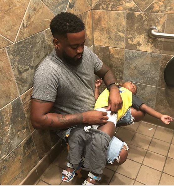 Father struggling to change son's diaper.