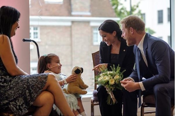 Prince Harry and Meghan Markle talking to a young girl at the Well Child Awards