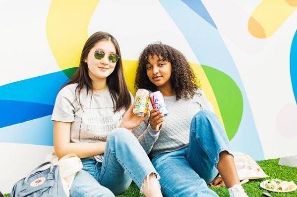 Two girls holding LaCroix cans