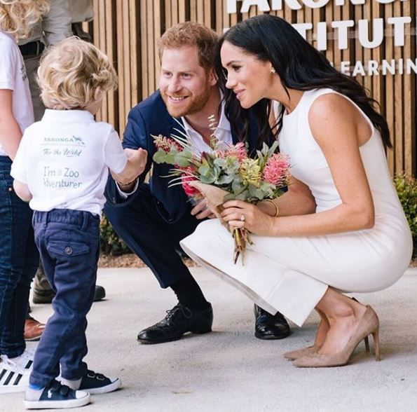 Prince Harry and Meghan Markle meeting a boy at the zoo