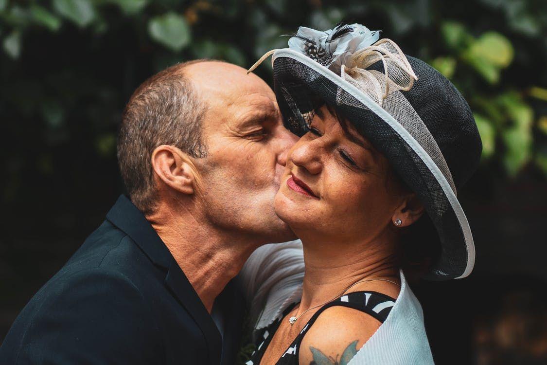 Man kissing a woman on her cheek