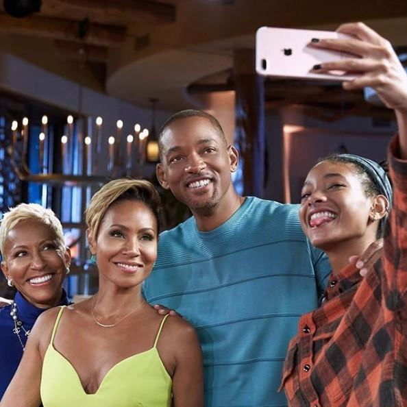Will Smith taking a photo with Jada, Adrienne, and Willow