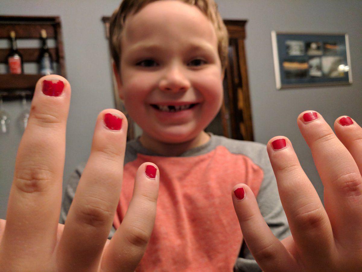 Sam wearing his bright red nail polish