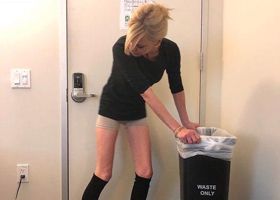 Anna Faris grabbing a trashcan while wearing bike shorts