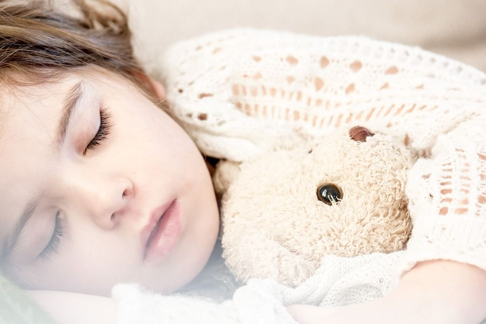 Girl sleeping with teddy bear