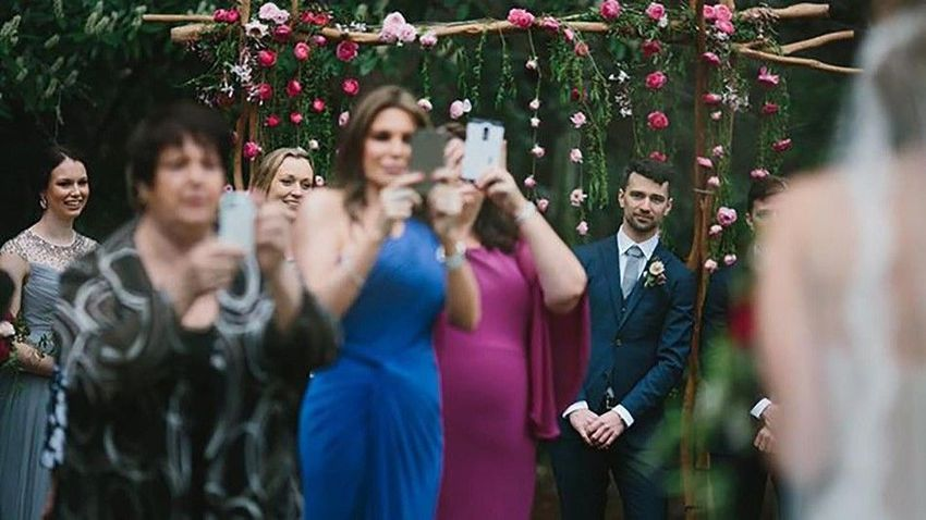 Wedding guests taking photos with their cellphones
