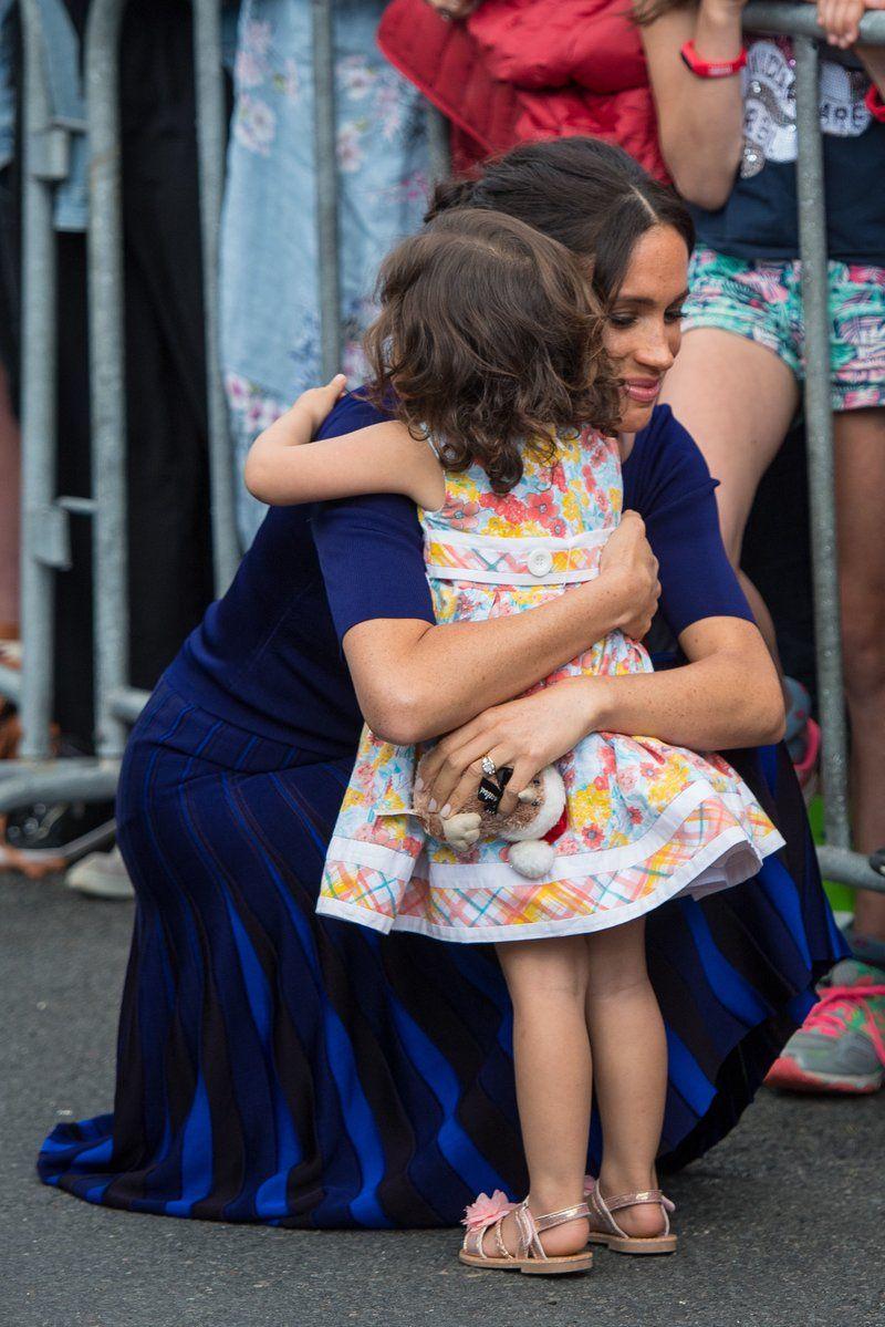 Meghan Markle hugging a child New Zealand Tour