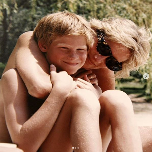 A young Prince Harry being embraced by Princess Diana.
