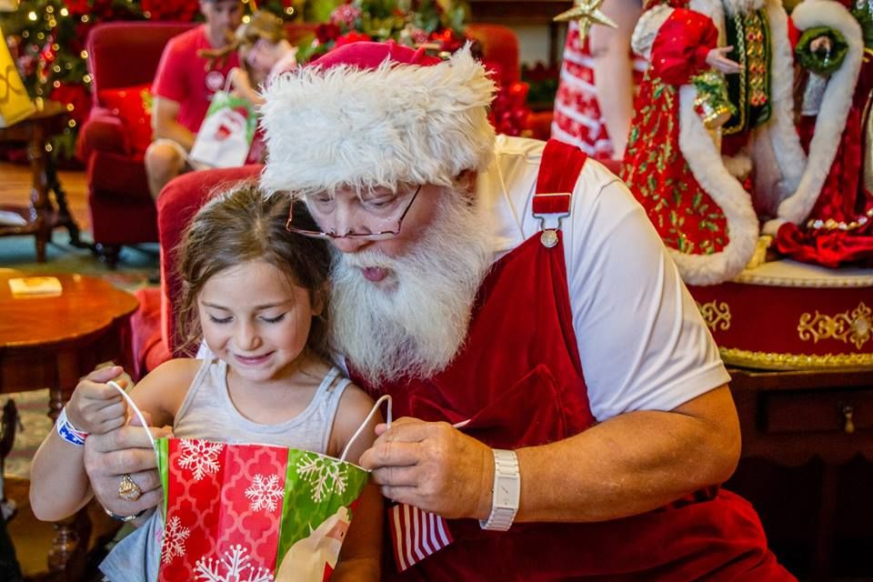 A little girl opening a gift with Santa Claus