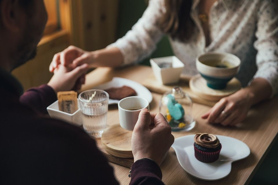 A couple holding hands over dessert