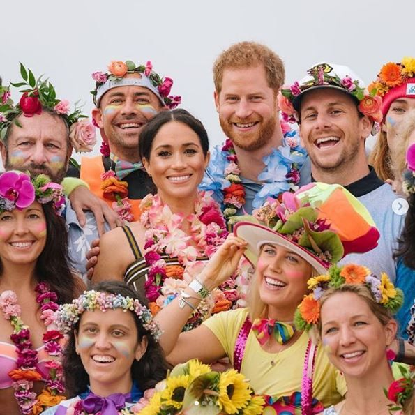 Prince Harry and Meghan Markle pose with fans at Bondi Beach.