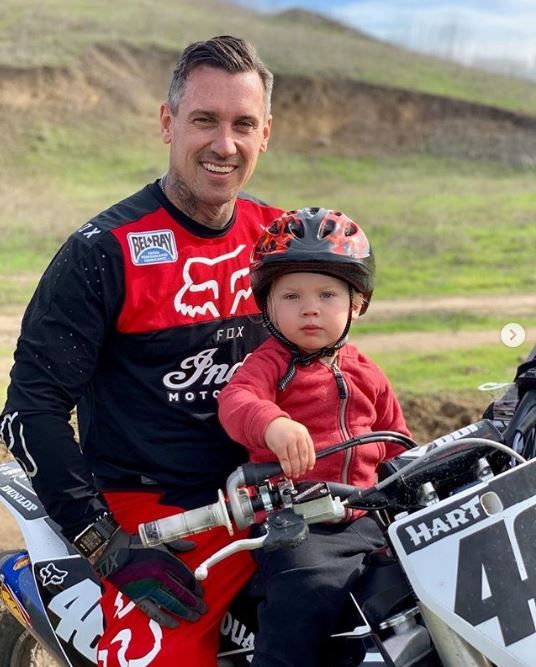 Carey Hart and son Jameson riding a dirt bike