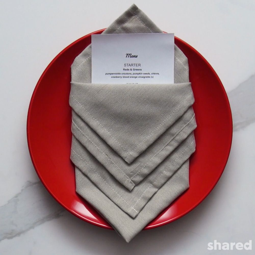 grey napkin folded with fancy technique red plate