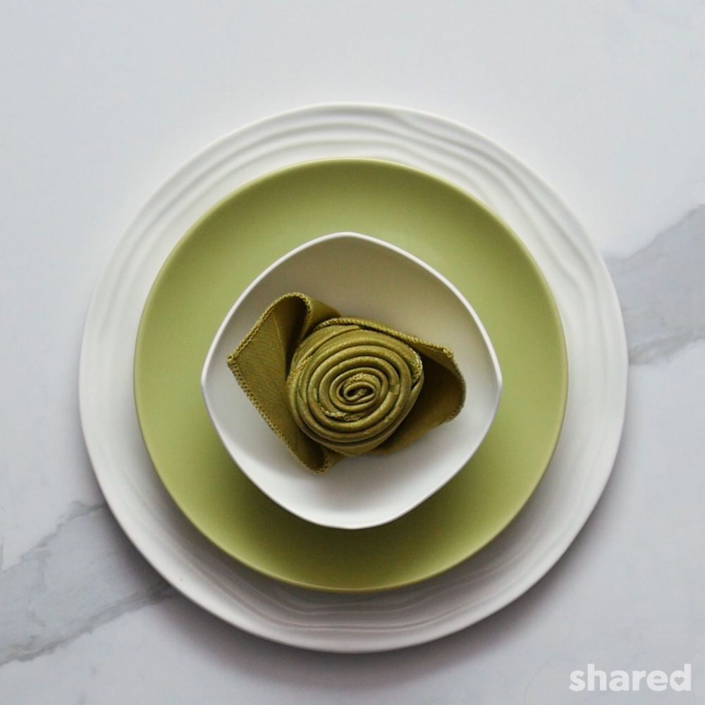 green and white place setting featuring green rosebud napkin fold