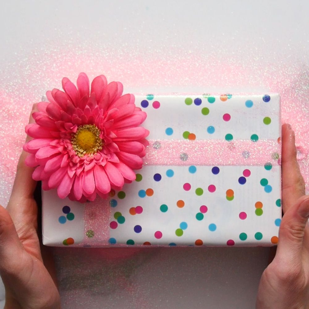 Birthday gift wrapped in multi colored polka dot paper finished with light pink glitter and a bright pink flower