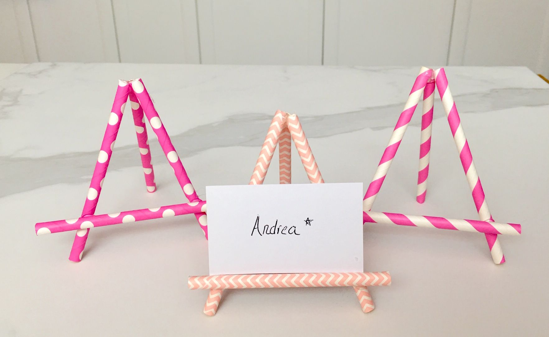 Three pink place card holders made out of paper straws