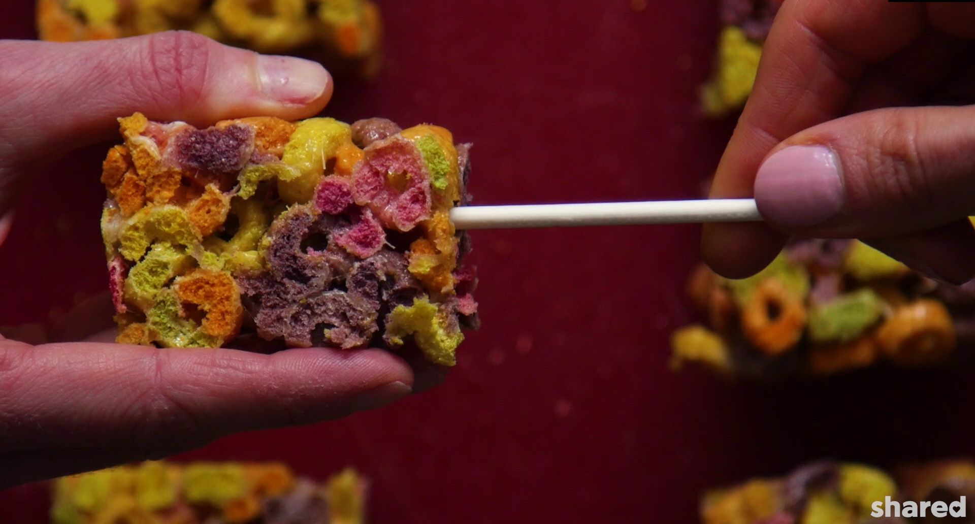 fruit loop square being stuck onto a cake-pop stick