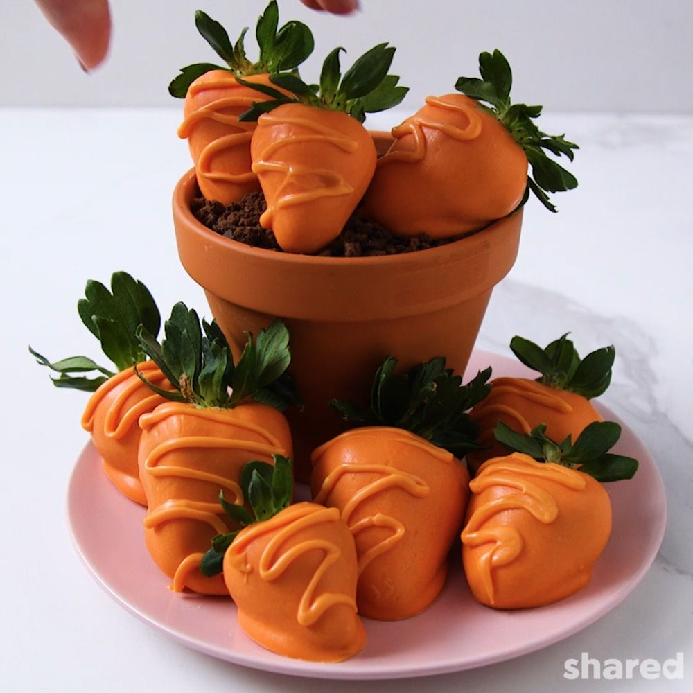 Strawberries on a pink plate dipped in orange chocolate to look like carrots