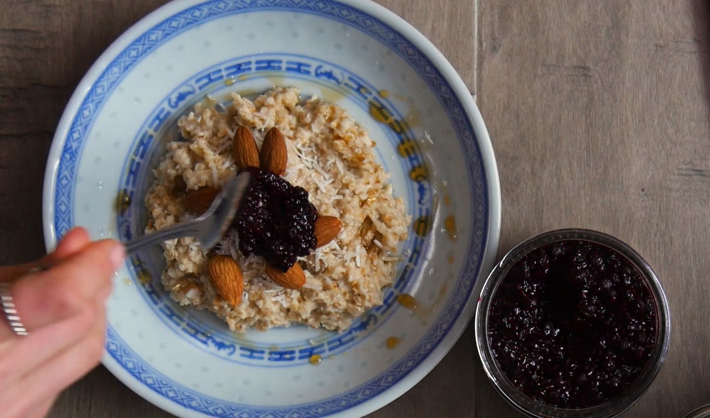 blueberry chia jam being spooned on top of oatmeal