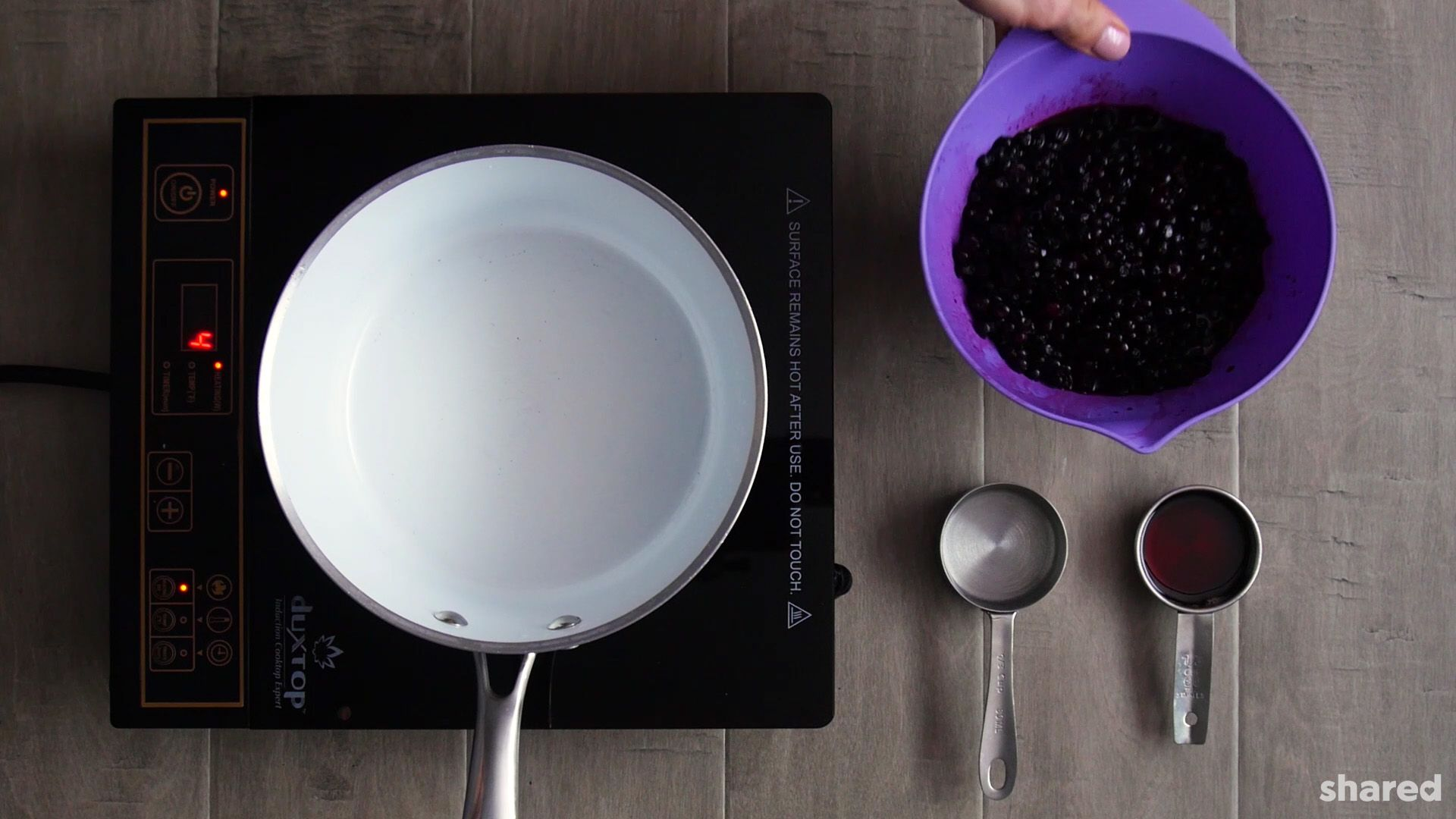 photo may contain a white saucepan on a stove top beside a purple bowl with frozen blueberries and and two stainless measuring cups of water and maple syrup