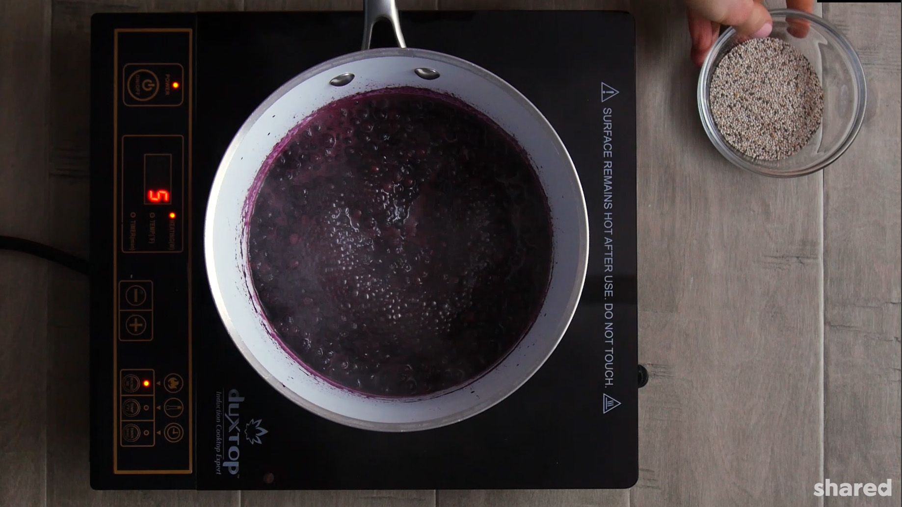 blueberry chia jam in a white saucepan simmering on a stove top