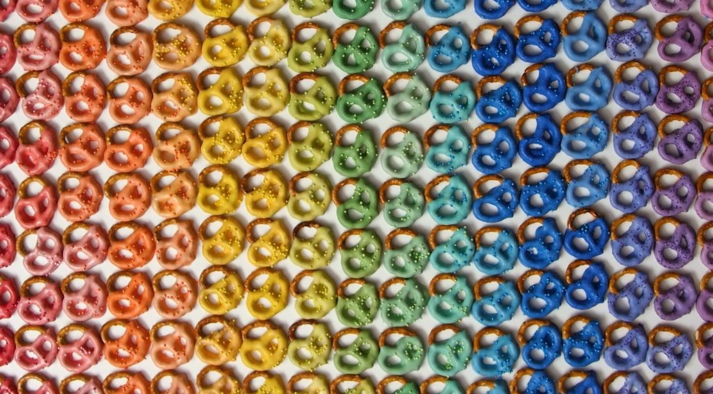 hundreds of chocolate covered pretzels in the colors of the rainbow lined up next to each other
