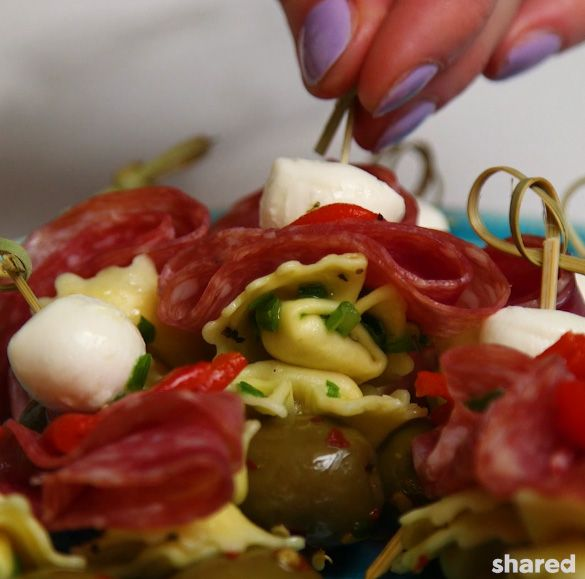 close up of an antipasto skewer being picked up off of a tray