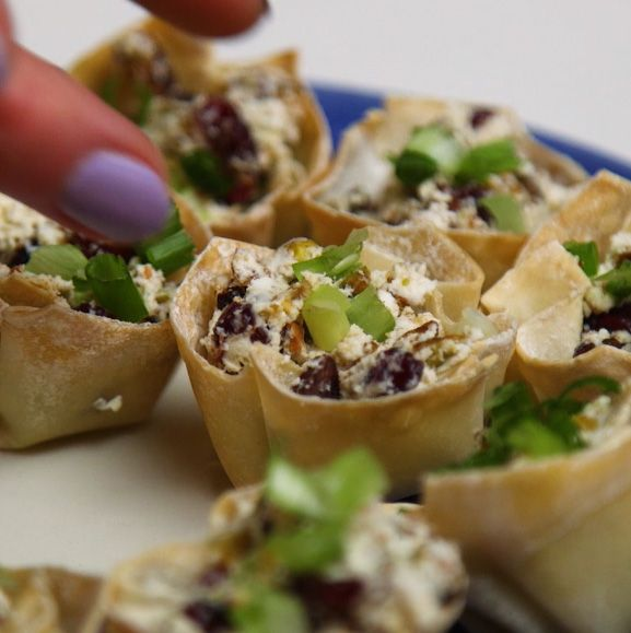 fingers grabbing for a pistachio goat cheese phyllo cup on a serving tray